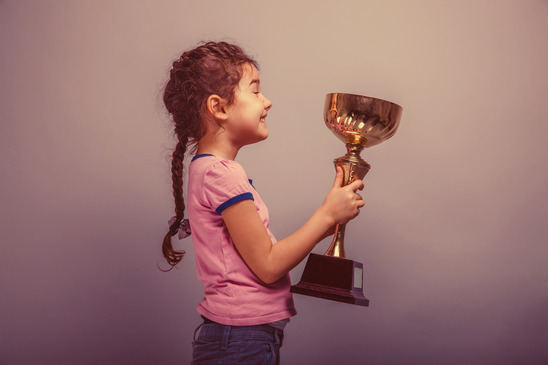 young girl holds trophy