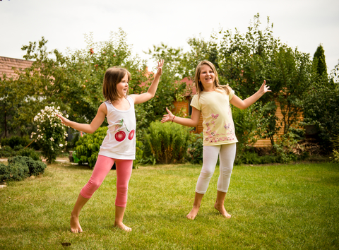 Children dancing happily in a yard