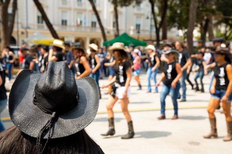 Black hat and group country dancing on city street